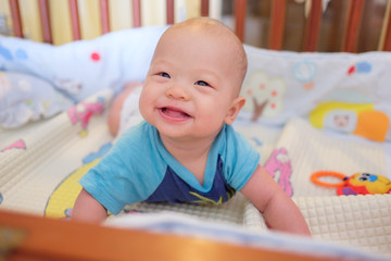 Cute little Asian 5 - 6 months old baby boy child at tummy time in baby cot / crib in bedroom at home day time; Newborn child relaxing. Nursery for young children. Soft and Selective focus
