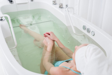 partial view of woman in swimming suit with towel on head relaxing in bath in spa salon