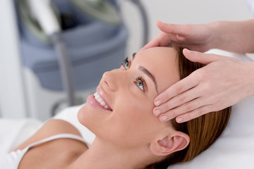 partial view of young woman getting head massage made by cosmetologist in salon