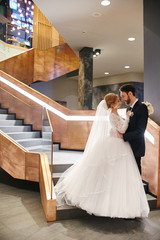 Bride and groom hugging and kissing while standing on the stairs. Wedding, gentle embrace of man and woman. The family, the husband and wife