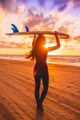 Surf girl with long hair go to surfing. Young woman with surfboard on a beach at sunset.