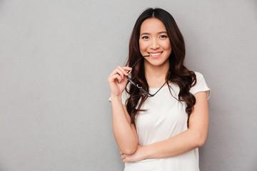Happy asian woman in t-shirt bites eyeglasses