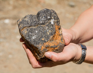 silver traces in the rock in his hand