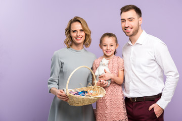 Parents and daughter holding basket with Easter eggs isolated on violet