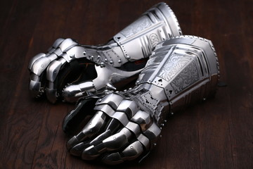 Medieval armor, detail of an ancient armor. Steel gloves on wooden background.
