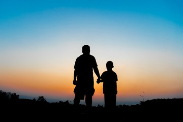Silhouette Father and son hold hands in evening time