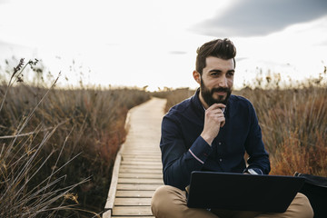Concentrated man relaxing on wooden pathway in field browsing laptop in sunlight.