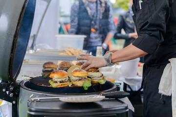 Chef making beef burgers outdoor on open kitchen international food festival event.