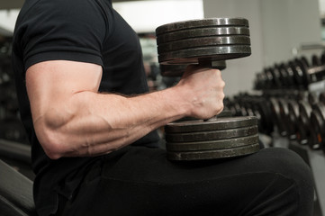 Muscular bodybuilder guy holding big black iron dumbbells in a gym. Man with big hand muscles working out in a gym. Gym and fitness details.