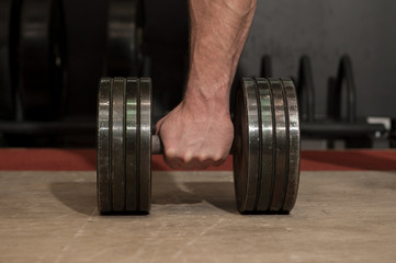 Bodybuilder with his strong, big arm picking up black metal dumbbell. Fitness and gym details.