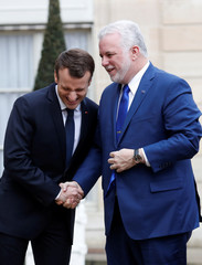 French President Emmanuel Macron greets Quebec Premier Philippe Couillard before a meeting at the Elysee Palace in Paris