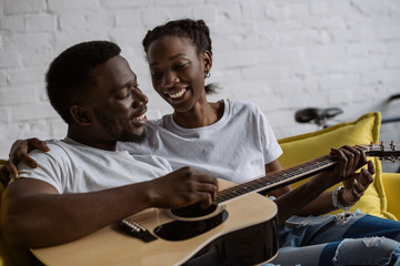 beautiful young woman looking at boyfriend playing guitar at home