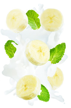 Flying banana slices with mint leaves and a spray of milk