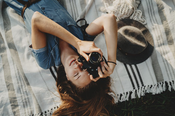 Beautiful young smiling girl with blond hair lying on a grass taking a photo on vintage film camera while walking in the city park, holidays lifestyle concept