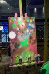 Easel with colorful spots at studio with colorful spray cans of aerosol paint