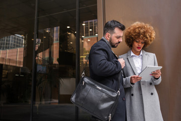 Stylish couple with tablet on street