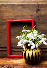 Snowdrop flowers in a vase on rustic wooden background