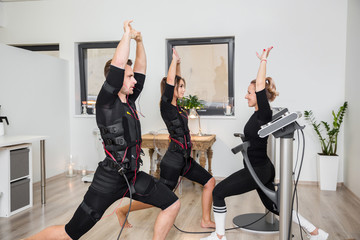 People doing ems exercising raising hands