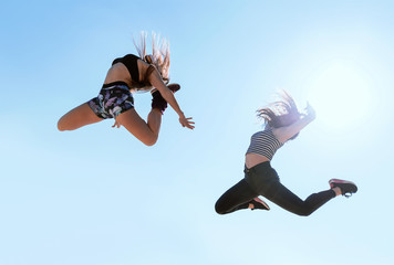 Women jumping in clear sky