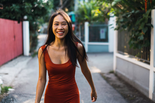 Portrait of cheerful woman walking on street