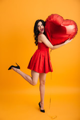 Full length photo of sexual woman with long dark hair in red dress hugging big valentine heart balloon with pleasure, isolated over yellow background