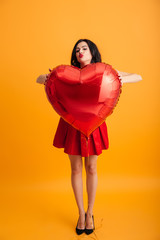 Full length image of fancy flirting woman with red lips giving kiss on camera while holding big heart shaped balloon, isolated over yellow background