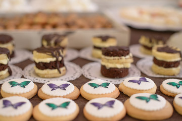 Assortment of small, flat, button-like cookies, ornate with colorful frosting butterflies, at candy and cake bar, at a wedding reception