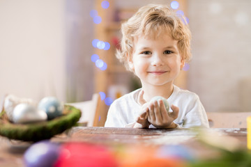 Portrait of adorable blonde boy looking at camera and smiling happily while celebrating Easter at home, copy space