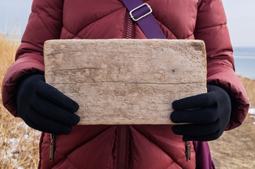 Wooden sign or board in female hands as a layout for the message text