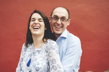 Mid aged couple smiling with red wall on background