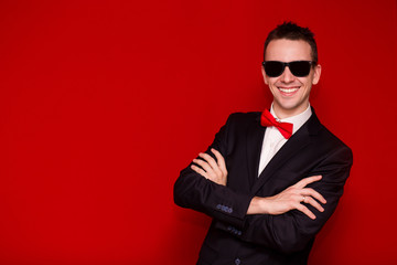 Portrait of smiling handsome stylish man in elegant black suit and sunglasses on red background. Business style. Fashionable image. Office worker. Sexy man standing and looking at the camera