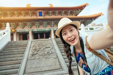 Happy Asian tourist taking a fun selfie