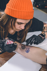 Woman tattoo artist during tattooing process