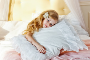 Sweet little girl hugging a pillow looking at the camera and smiling sitting on bed at home in my room