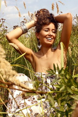 Portrait of a beautiful girl in a white dress in a summer field