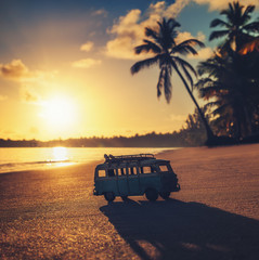 Vintage miniature van on the tropical beach at sunrise