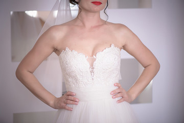 Cropped frontal shot of white Caucasian woman with red lips wearing bridal white ballgown and holding hands on the waist, morning wedding preparation and wedding gowns ideas