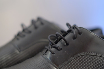 Close-up cropped shot of used black male leather shoes, elegant footwear polishes and ready to be worn again