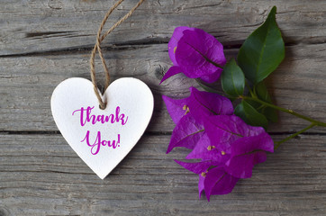 Thank You or thanks greeting card with bougainvillea flowers and decorative white heart on wooden background.Selective focus.
