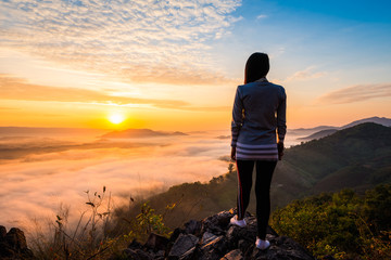 Young woman standing on top of the mountain watching the sun rise with fog
