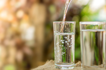 Pouring fresh water on drinking glass over nature sunlight morning ,freshness concept background