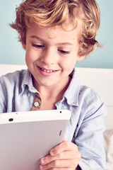 Little boy sitting and using tablet