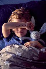Boy sleeping on bed with eyes closed drawn on arm
