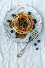 blueberry pancakes with blueberries sprinkles around on flower plate on white tablecloth flat lay
