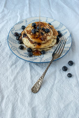 blueberry pancakes with blueberries sprinkles around on flower plate on white tablecloth
