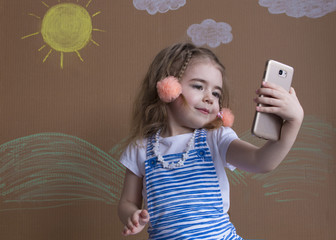 Emotional portrait cute girl and pigtails makes selfie with a cell phone. Adorable smiling toddler kid taking a selfie photo with smartphone