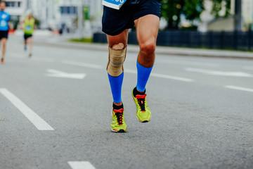Fotomurales - legs runner men in compression calf sleeves and kneepad running in city