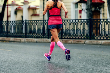 Fototapete - female runner in pink compression calf sleeves running marathon under rain drops
