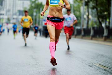 Wall Mural - female athlete runner overtake group man runner in city marathon