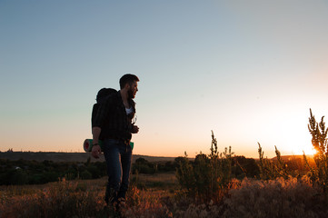 Traveler with backpack standing on a rock and enjoying sunset